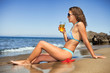 Young woman drink cocktail on beach