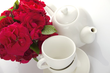 White crockery for tea and a bouquet of roses