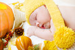 Newborn kid among pumpkins