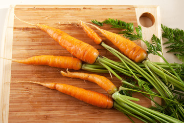 Fresh carrots on wooden chopping board