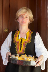 Woman in Bulgarian folk costume with mushrooms
