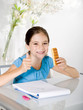child eats snack while studying