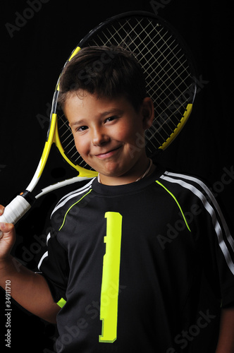 Tennis boy smiling isolated in black