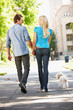 Couple walking with dog in city street