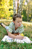 A boy with apple reads book on the grass