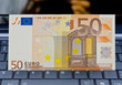 Euro banknote on laptop's keyboard