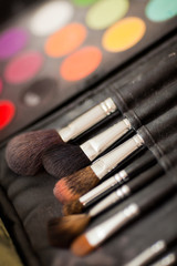 cosmetic brushes. multicolored eye shadows with cosmetics brush