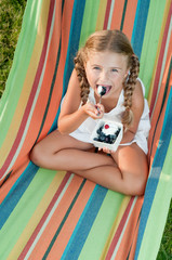 Cute girl eating blueberries in colorful hammock