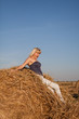 The beautiful girl jumps off from a haystack