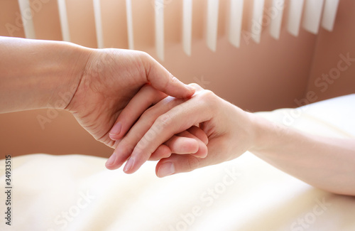 Holding hand of a sick loved one in hospital bed