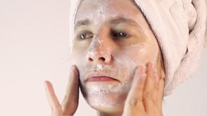 Joven tres cuartos de perfil aplicando crema para cuidado facial