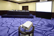 Big table with microphone near screen in bright conference hall,