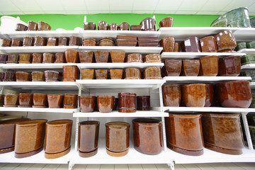 Shelves with variety of brown clay flowerpot inside supermarket