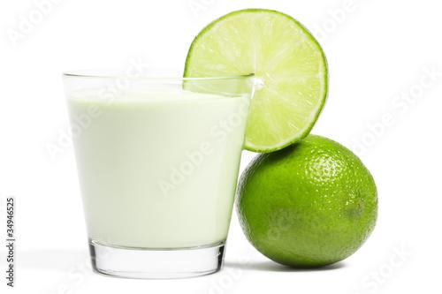Leinwandbild Motiv limonenscheibe an einem milchshake glas und limone