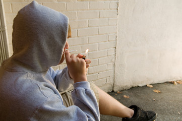 teen boy lighting a joint