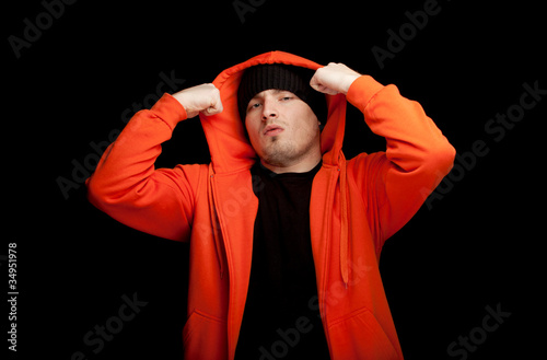 young man in orange sweatshirt, black background