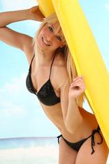 Frau mit Luftmatratze am Strand