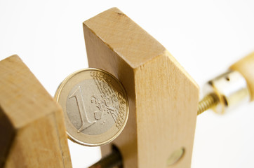 Euro coin under pressure in  a wooden clamp