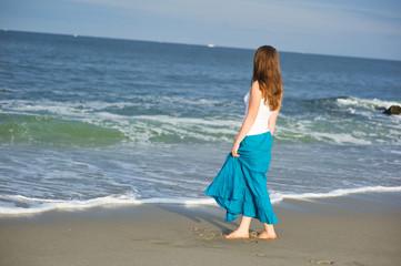 Beautiful young woman walks along the ocean