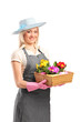Young florist holding a basket with flowers