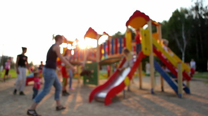 parents play with their children on the playground. defocus