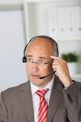 mann mit headset tippt sich an die stirn