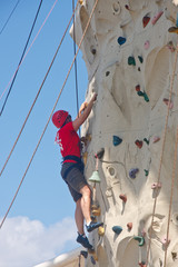 Man in Red Shirt Climbing Rock Wall