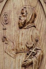 scultura di frate santo su portone di chiesa in legno