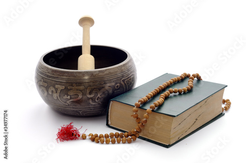 Singing bowl, book and wooden rosary isolated on a white.
