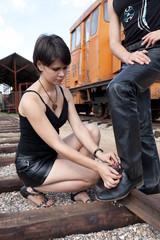 Девушка завазыват шнурок на ботинке.