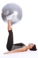 Strong young woman exercising legs with ball