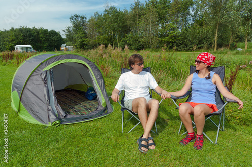 Family vacation in camping. Happy couple near their tent