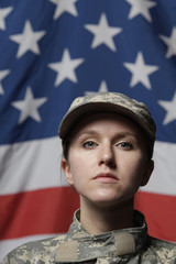 Female soldier in front of US flag, vertical