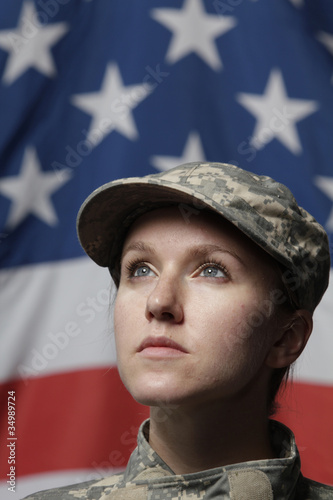 Female soldier in front of US flag looking up, vertical