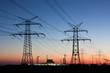 Strommasten in der Abenddämmerung, am Horizont Kernkraftwerk