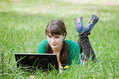 young sexy girl with a laptop in the grass