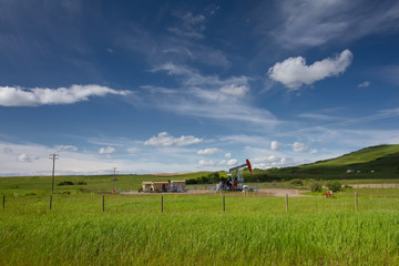 Canadian landscape with green grass, blue sky and pumpjack