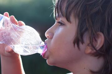 bambino beve acqua dalla bottiglia
