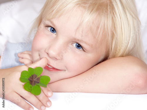 Portrait of adorable little girl brings luck with shamrock