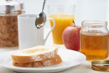 pouring honey on sliced bread