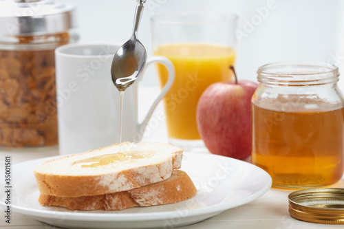 pouring honey on sliced bread