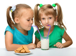 Two little girls are drinking milk