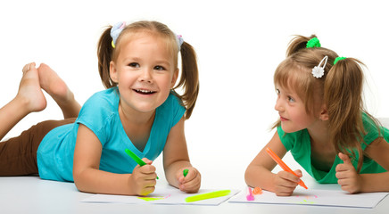 Two little girls draw with markers