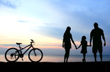Fototapety Mother and kids silhouettes on beach at sunset