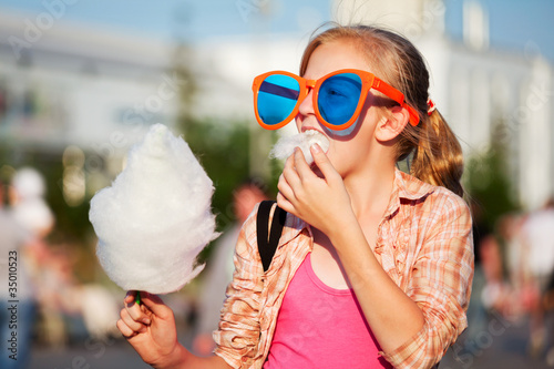 Girl eating cotton candy - 35010523