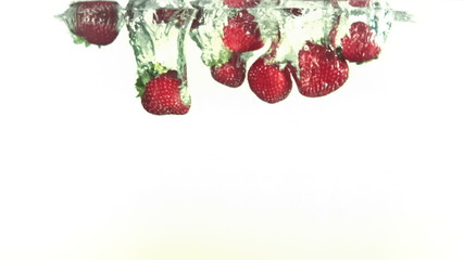 Red strawberries falling into water