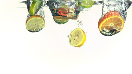 Slices of oranges, limes and lemons falling into water