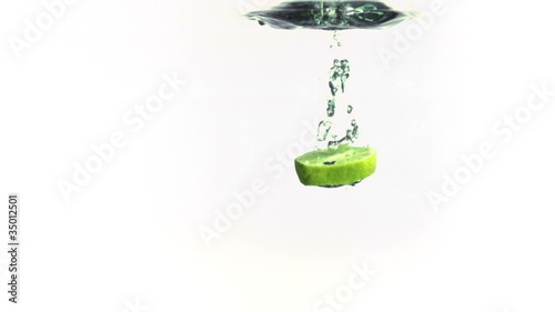 Slice of Lime falling into water