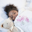 Mixed race girl in bed with teddy bear