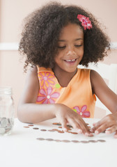 Mixed race girl counting coins